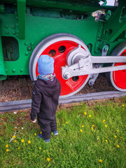 A little boy touches the wheels of a locomotive standing on the rails in the middle of a clearing and decorated in bright colors