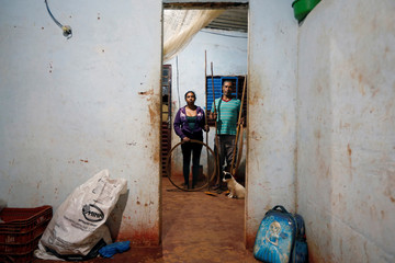 Sales Felix and Sebastiana Ferreira pose for a picture in his accommodation after working on a coffee farm, in Campos Altos