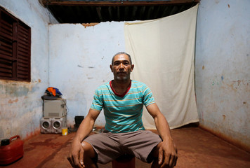 Sales Felix poses for a picture in his accommodation after working on a coffee farm, in Campos Altos