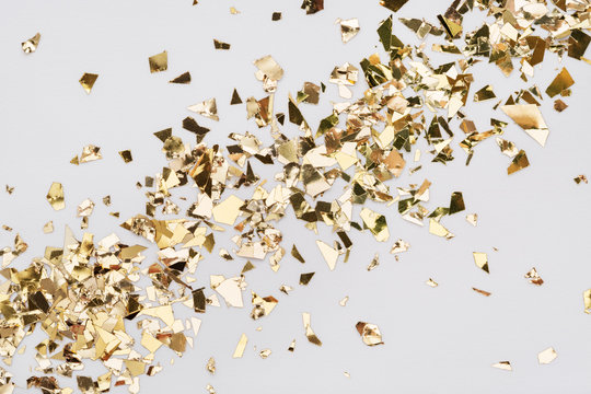 Gold leaf confetti on white background. Festive, party or holiday glitter backdrop. Flat-lay, close-up. Diagonal spread.