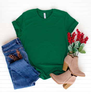 Green shirt top view and styled with Christmas items - white background