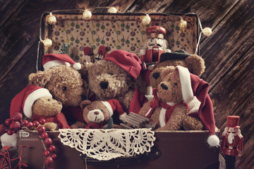 old suitcase full of teddy bears in Santa caps in retro style