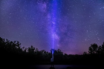 Person directing a purple light of the lamp into the breathtaking sky full of stars