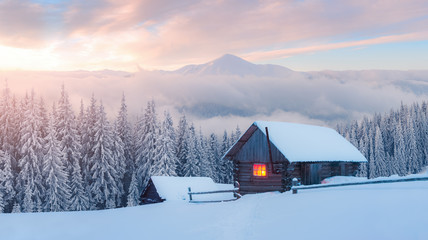 Photo sur Toile Taupe Fantastic winter landscape with wooden house in snowy mountains. Hight mountain peaks in foggy sunset sky. Christmas and winter vacations holiday concept