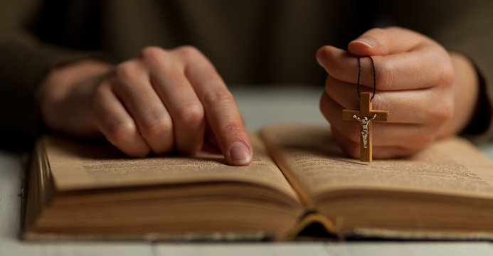 Reading God's commandments in the Bible, close-up of a hand with a crucifix.