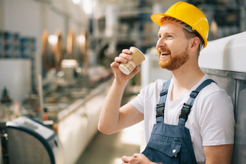 Fototapeta Portrait of young worker drinking coffee in factory. obraz