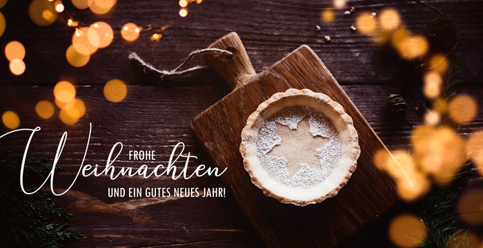 Traditional homemade Christmas pie on dark wooden background, with romantic lights and greeting text in german language/ banner, header / flat lay, top view