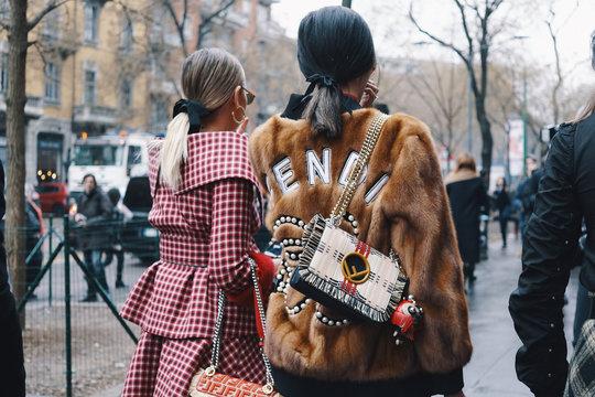 Milan, Italy - February 22, 2018: Fashionable girls wearing Fendi clothing posing after Fendi fashion show during Milan Fashion Week - street style concept