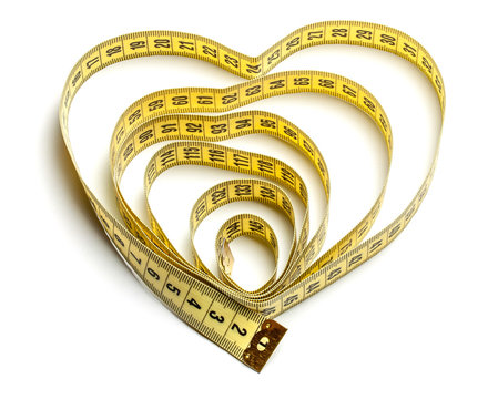 Heart made of yellow measuring tape isolated on white background