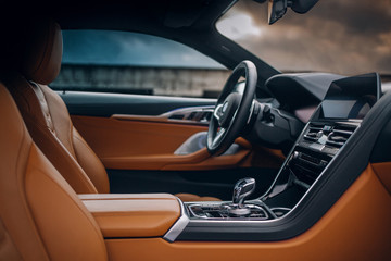 Modern supercar interior with leather panel, multimedia and dashboard