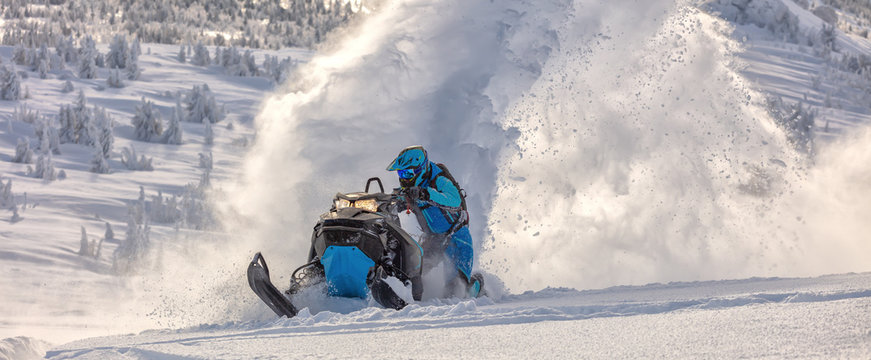Pro snowmobiler makes a turn and lets a flurry of snow spray from under the caterpillar. sports snowmobile in the mountains. bright skidoo motorbike and suit without brands. Winter fun moto extreme