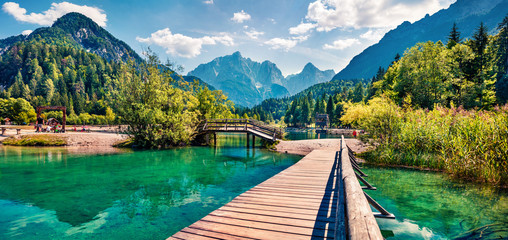 Wooden bridge over the Jasna lake. Panoramic summer view of Julian Alps, Gozd Martuljek location,...