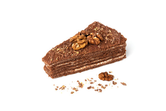 Slice of chocolate cake with milk filling and walnut isolated on white background.