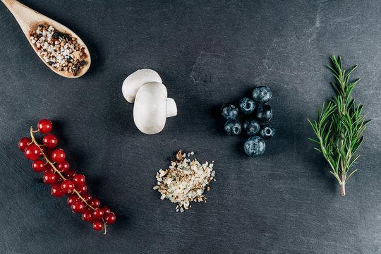 Verschiedene Zutaten wie Blaubeeren, Gewürze, Rosmarin, Champignons und Johannisbeeren auf einer Schieferplatte