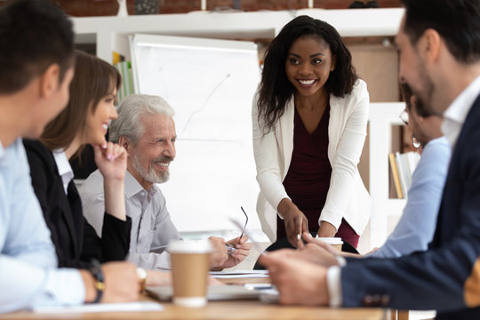 Diverse businesspeople gathered together for negotiations lead by african businesswoman