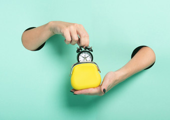 Female hands hold alarm clock and wallet through a hole on neon mint background. Time is money concept.