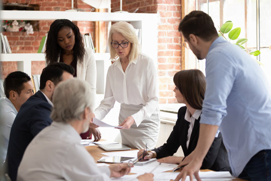 Diverse team and aged boss do paperwork analyzing financial report