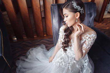 Top side view of a beautiful elegant brunette Asian in an expensive wedding dress sitting on a chair in a hotel room waiting for the celebration. Wedding and gala party concept