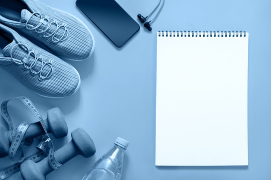Sport and fitness equipment with sneakers and headphones on blue. Blank with space for text. View from above. Trendy color Classic clue of the 2020 year.