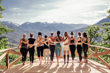 Obraz Rear view of a group of slim body-positive sportive active friendly women doing fitness and yoga together among mountain ecologically clean nature. Ecological Sports Tourism Concept - fototapety do salonu