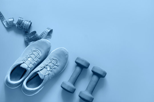 Sport and fitness equipment, dumbbells, fitness shoes, measuring tape on blue. Top view, space for text.