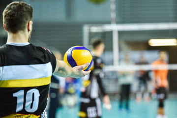 Volleyball player holds the ball before the service