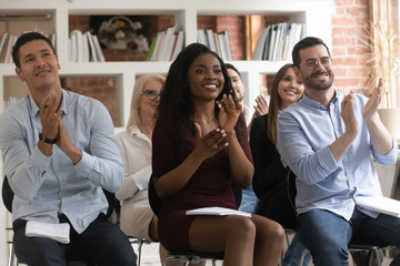 Diverse entrepreneurs seminar participants clap hands expressing gratitude for speech