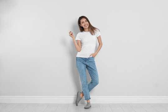Young woman in stylish jeans near light wall