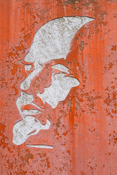 Shabby white silhouette of Lenin on a red background.