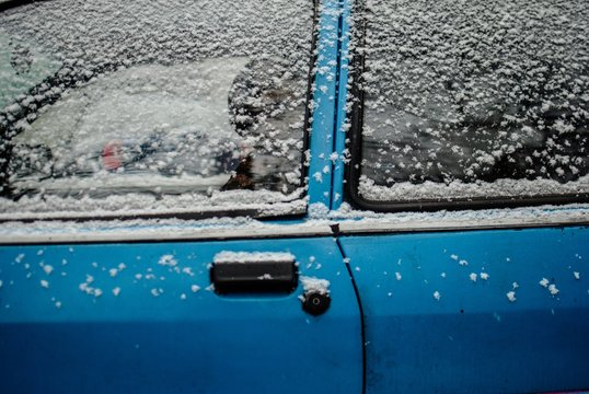 Old blue car covered with snow