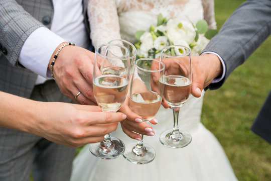 wedding bouquet of flowers in the hands of the bride.glasses with champagne in hand.