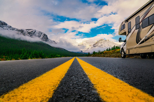 Close up of Yellow Highway Lines With Motorhome In Vast Mountain Landscape Scene
