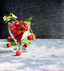 Raspberry berries with green leaves in a glass bowl on a gray background.