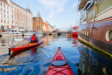 A woman is paddling a sea kayak early in the morning into the canal of Nyhavn, Copenhagen, Denmark.