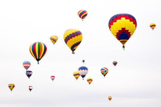 USA, New Mexico, Albuquerque. International Balloon Festival. Hot air balloons rise into a white sky after launch.