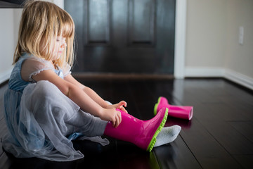 Preschool girl practices putting on rain boot