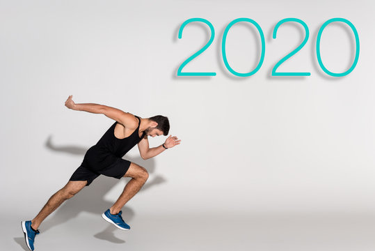side view of sportsman running on white background with 2020 lettering