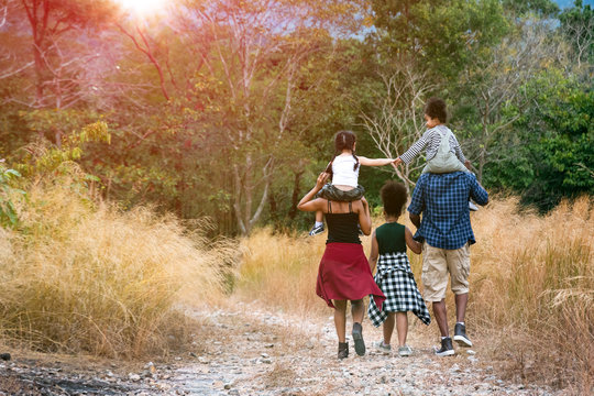 Rear view of big mixed race family, father and mother carrying our daughter walking along yellow field to campsite. Travel vacation concept.