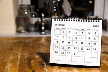 December 2020 calendar - month page on wooden table in the kitchen