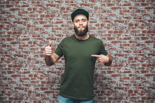 City portrait of handsome hipster guy with beard wearing a blank green military t-shirt and blank black cap standing on a brick wall background. Empty space for your logo or design. Mockup for print.