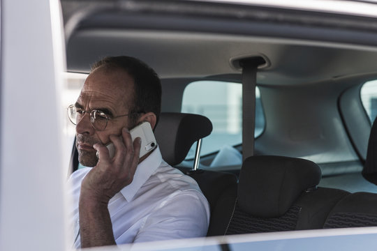 Portrait of mature businessman on the phone in car