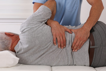 Chiropractic treatment, Back pain relief. Physiotherapy for senior male patient, Kinesiology