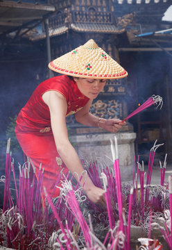 Woman lighting incense sticks in temple