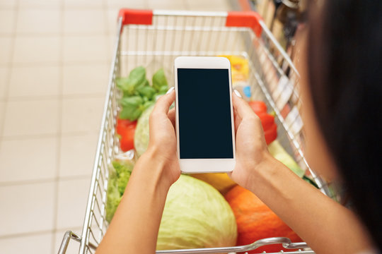 Young adult woman holding modern smartphone in supermarket