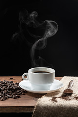 Spoed Fotobehang Cafe Warm coffe smoke, with .coffee beans. wooden spoon with coffe on wooden base, on dark background.