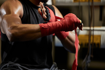 Midsection of male boxer wrapping bandage on hand