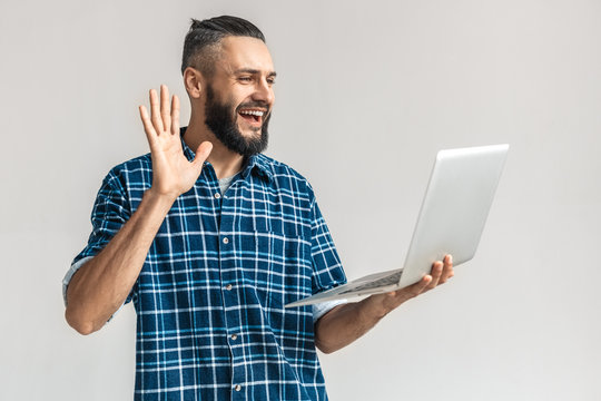 Adult bearded man waving hello, holding laptop in hand