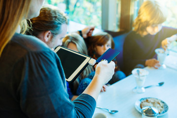 Cropped image of waitress using credit card on reader attached to digital tablet with family in background in restaurant
