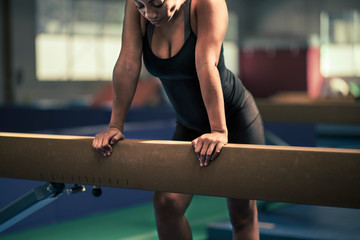 Midsection of female gymnast leaning on balance beam at gym