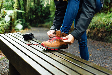 Female hiker tying shoelace on bench in forest